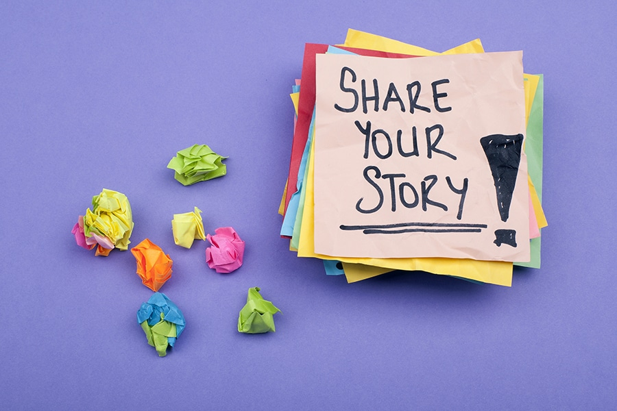 Share your story note on paper with purple background