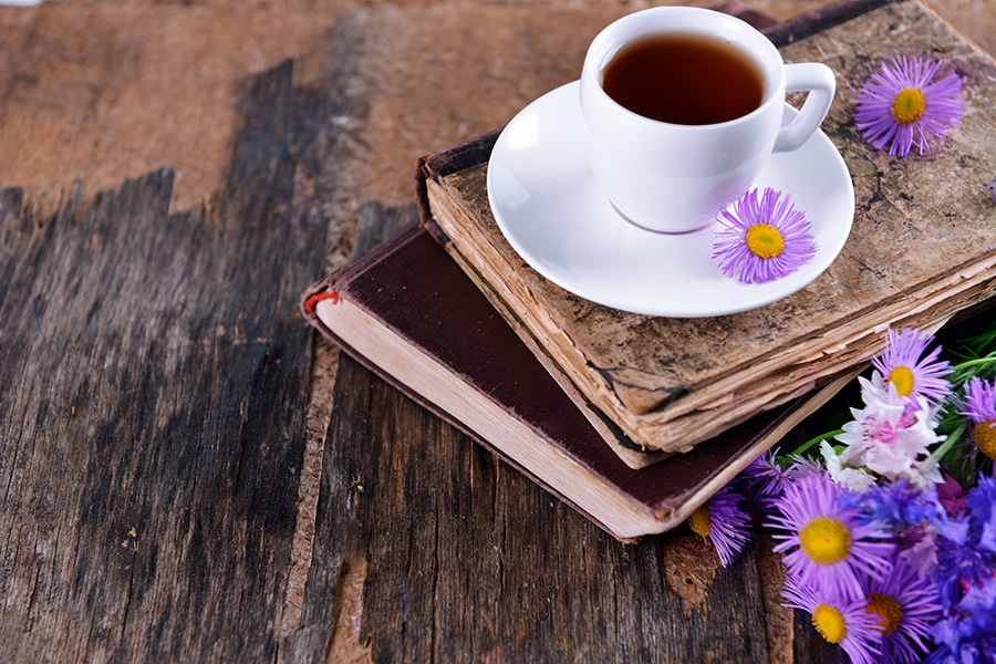 Old books with beautiful flowers and cup of tea on wooden table
